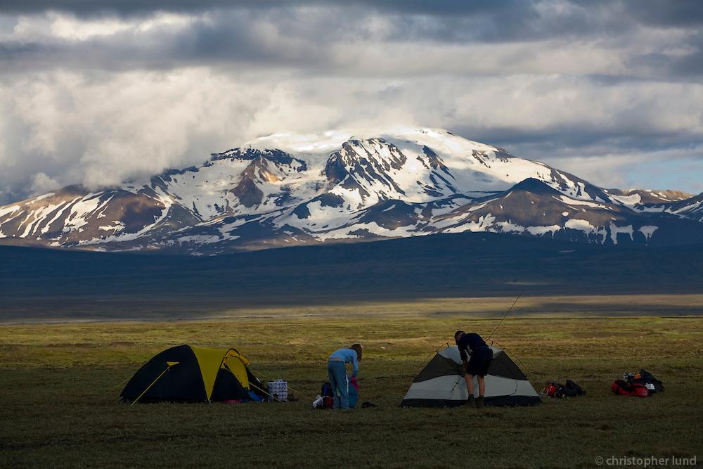 Hikers camping at Sau&eth;afellsalda. Mountain Sn&aelig;fell in background. Highlands of Iceland.<br /> <br /> G&ouml;ngumenn a&eth; tjalda vi&eth; Sau&eth;afells&ouml;ldu, Sn&aelig;fell ba&eth;a&eth; kv&ouml;lds&oacute;l &iacute; baks&yacute;n.