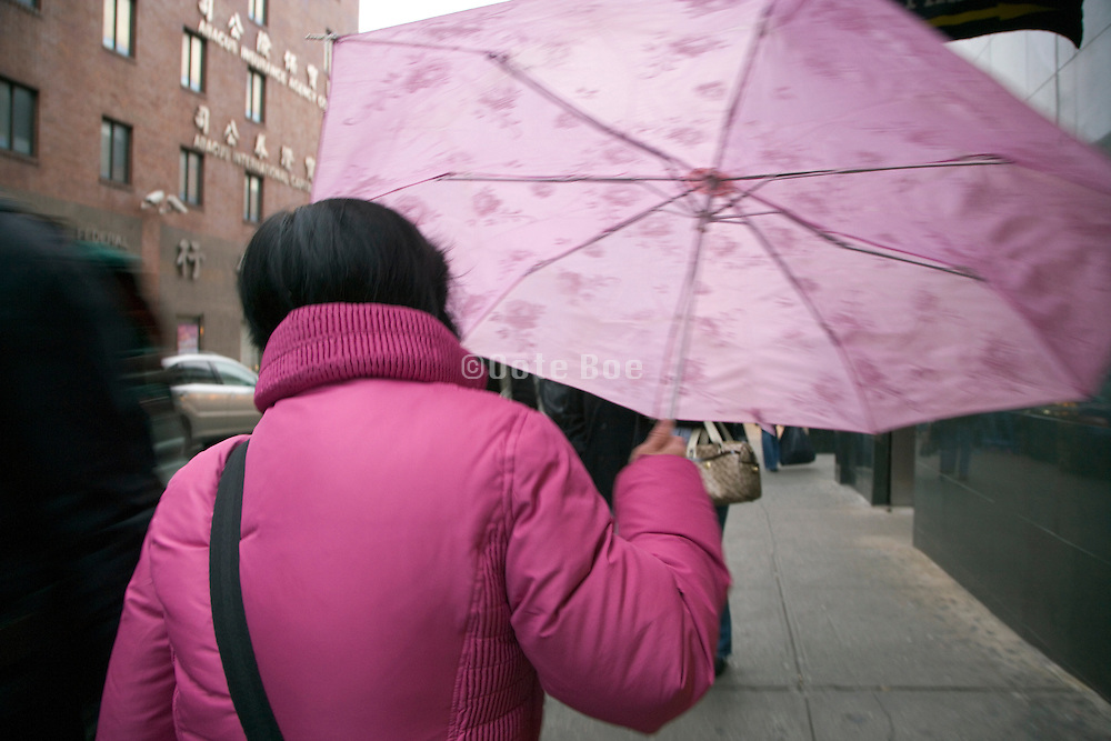 woman dressed in a pink winter coat with pink umbrella