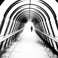 Lone female figure walking along modern foot bridge