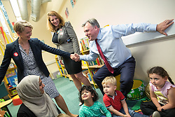 © Licensed to London News Pictures . 14/06/2016 . Blackburn , UK . Yvette Cooper MP helps her husband , former MP Ed Balls , stand up from a child's seat during a campaign for Remain , in the EU referendum , at Shadsworth Children's Centre in Blackburn . Photo credit : Joel Goodman/LNP