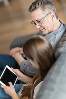 High angle view of father and daughter using digital tablet at home