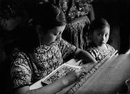 Young indigenous woman works on a back-strap loom while younger girl looks on, San Lucas Sacatepequez, Guatemala.