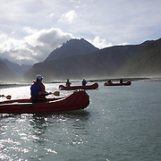 People on the Dart River Funyak Safari with Dart River Jet Safaris. The  unique adventure combines exhilarating wilderness jet boating with unique Funyak inflatable canoes used to explore the magnificent World Heritage wilderness within Mt Aspiring National Park. Professional guides take participants through dramatic landscapes, paddling along channels of the glacier fed Dart River's braided river system as well as along hidden side streams, rock pools and dramatic chasms. The tour is based at Glenorchy and provides transport from Queenstown, Dart River Safaris. Glenorchy, New Zealand. 13th April 2011. Photo Tim Clayton..