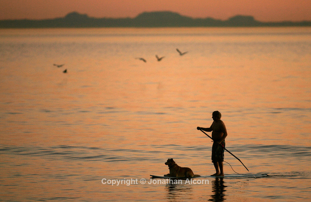 Jan 14, 2009 - Pacific Palisades, California, USA - SYD LOVELACE and his dog Booda paddle board over calm ocean waters at off Will Rogers State Beach just after the sunset on a winter day with summer like temperatures in Southern California..(Credit Image: © Jonathan Alcorn/ZUMA Press)