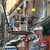 Freezing Perthshire....07.12.10  <br /> As temperatures plummeted overnight to minus 18, Tayside Fire & Rescue were inundated with 999 calls regarding dangerous ice hanging from buildings...Pictured are Firefighters Chris Phillips and John Christie removing ice from buildings in Perth's High Street.<br /> Picture by Graeme Hart.<br /> Copyright Perthshire Picture Agency<br /> Tel: 01738 623350  Mobile: 07990 594431