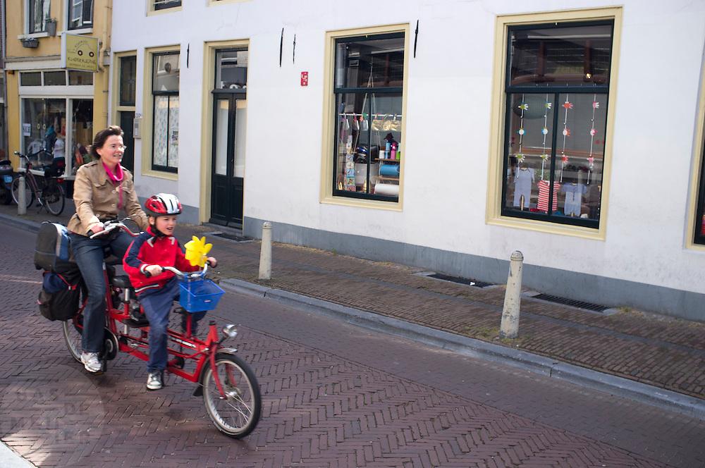 Een moeder fietst met een kind op de tandem door Utrecht.<br /> <br /> A mother is cycling on a tandem with a child.