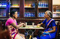Jaffna, Sri Lanka -- February 9, 2018: Two women eating lunch at a small cafe.