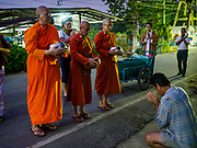 13 JANUARY 2019 - NAKHON PATHOM, THAILAND: Female monks from Wat Songdhammakalyani chant after a man in the community gave the monks food on their alms rounds. The Sangha Supreme Council, Thailand's governing body of Buddhist monks, bans the ordination of female monks, but hundreds of Thai women have gone abroad, mostly to Sri Lanka and India, to be ordained. There are about 270 women monks in Thailand and about 250,000 male monks. There are 7 monks and 6 novices at Wat Songdhammakalyani in Nakhon Pathom. It was the first temple in Thailand to have female monks. The temple opened 60 years ago and has always been a temple of women monks. Women can be ordained as novices in Thailand, but to be ordained as a full monk would require the participation of 10 female monks and 10 male monks, and male monks in Thailand are barred from participating in women's ordination ceremonies.     PHOTO BY JACK KURTZ