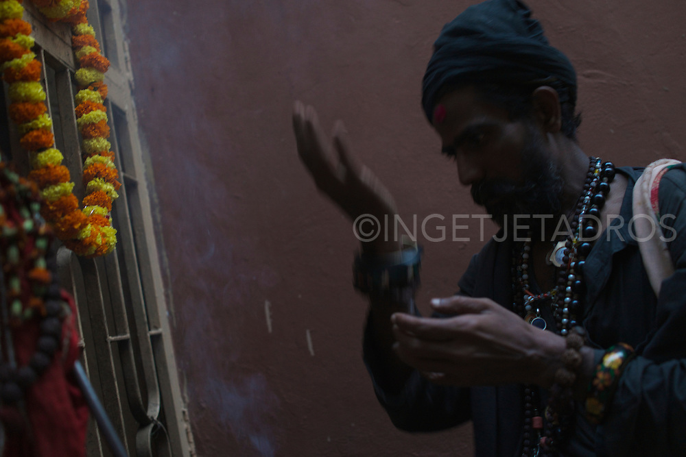 Rahm during worship at an Aghori Temple. He offers flowers and sweets, which he will sprinkle with some alcohol, candles and incense are lit and left burning. Varanasi, India.