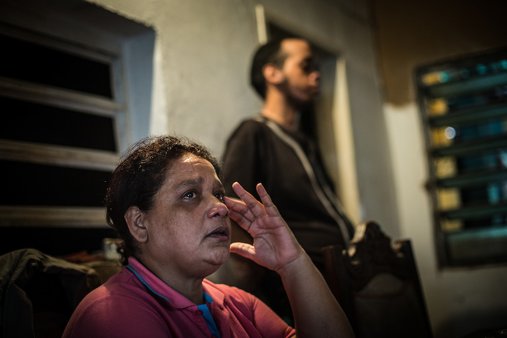 "MARACAY, VENEZUELA - JULY 15, 2016: Evelin RodrÍguez (left) cries in frustration while explaining how difficult her life is caring for her two schizophrenic sons, Gerardo and Accel, in a country suffering from severe shortages of medicines, including the psychiatric drugs that she needs to keep her sons' conditions stabilized. It is an exhausting task taking care of them and going from pharmacy to pharmacy for hours searching for the medicines that her sons need, that she is rarely able to find. She copes by reducing their doses, and by sharing their prescriptions depending on which son needs the medicine the most each day. Evelin is a lawyer, but has quit all of her work since Accel attempted to cut off his arm after three weeks without his medicine. Evelin now spends her days looking after Accel and Gerardo, too afraid to leave them alone because they might hurt themselves.  ""I am tired,"" she said. ""This is too much sometimes"". PHOTO: Meridith Kohut for The New York Times"