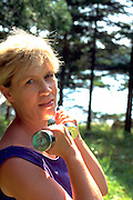 Woman age 56 resting during outdoor workout at summer home.  Cedarville Michigan USA