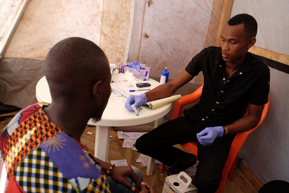 Mohamed Camara (left) is tested for HIV by activist Mamadou Alpha Diallo at the MSF mobile clinic in the neighbourhood of Sangoyah Market, Conakry, Guinea on March 17, 2016. MSF launched a HIV testing campaign in Conakry with the support of health authorities moving throughout several neighbourhoods throughout 2016.<br /> <br /> Despite countries in West and Central Africa having a relatively low HIV prevalence (