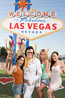 Women and Elvis impersonator posing in front of Las Vegas welcome sign, Nevada, USA