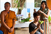 28 JUNE 2011 - CHIANG MAI, THAILAND:   A family member cuts a lock of hair from the head of a man being ordained as a Buddhist monk at Wat Phrathat Doi Saket a large temple complex in Chiang Mai, Thailand. The temple at Doi Saket is said to have been built in the year 1112, but it has been renovated several times since then. Most Thai males enter the Buddhist clergy, called the Sangha, at least once in their lives. Their stay in the monastery can be as short as one week or a lifetime committment, depending on the man.  PHOTO BY JACK KURTZ