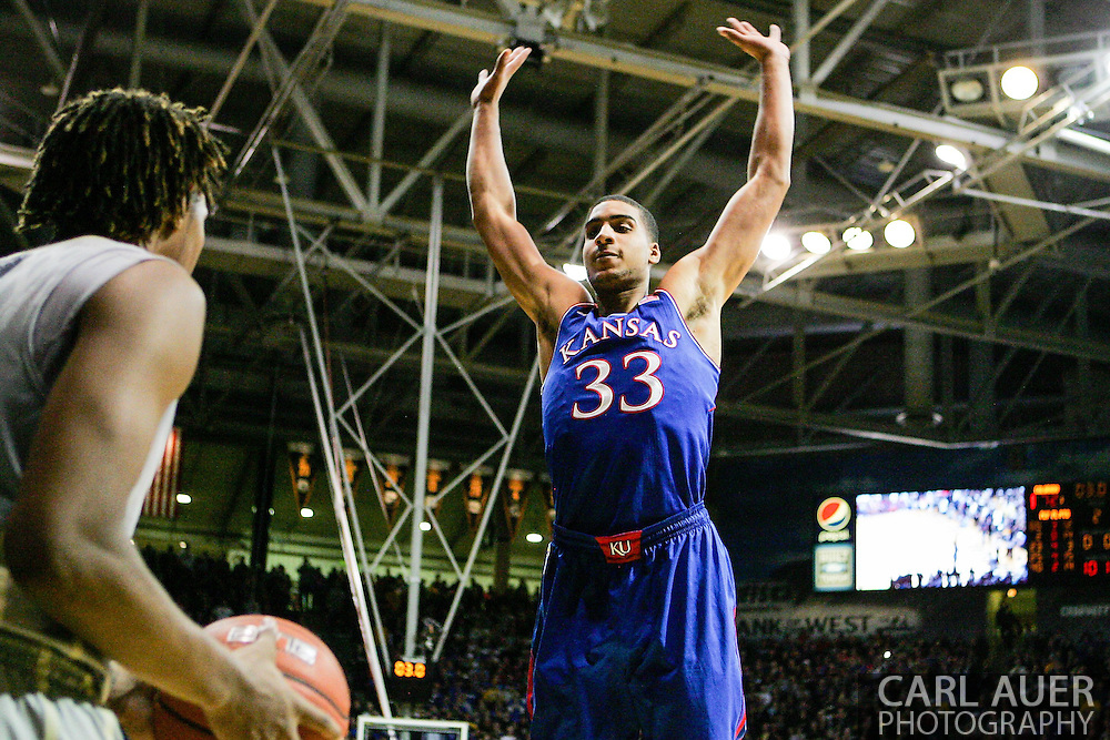 December 7th, 2013:  With the score tied 72-72, Colorado Buffaloes sophomore forward Xavier Johnson (2) looks to pass the ball by the defense of Kansas Jayhawks redshirt freshman forward Landen Lucas (33) in the final seconds of the NCAA Basketball game between the Kansas Jayhawks and the University of Colorado Buffaloes at the Coors Events Center in Boulder, Colorado