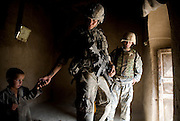 Private Timmy Mitchum of the 82nd Airborne's 1/508 Alpha Company, Third Platoon comforts an Afghan child while searching his home near Sangin, Helmand province, Afghanistan on Sunday, April 15, 2007.