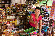 02 MARCH 2014 - MYAWADDY, KAYIN, MYANMAR (BURMA): A vendor gives change to a customer in the market in Myawaddy, Myanmar. Myawaddy is separated from the Thai border town of Mae Sot by the Moei River. Myawaddy is the most important trading point between Myanmar (Burma) and Thailand.    PHOTO BY JACK KURTZ
