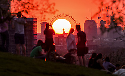 **2018 Pictures of the year by London News Pictures**<br /> © Licensed to London News Pictures. 19/04/2018. London, UK. Members of the public watch from a high point in Greenwich Park in London as the sun sets behind the London Eye, on a warm spring evening. Photo credit: Micheal Tomas/LNP