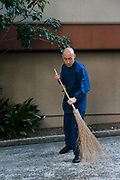 """Priest Matsumoto Shoukei cleaning at a """"Temple Morning"""" cleaning session. Komyoji Temple, Kamiyacho, Tokyo, Japan, April 13, 2019. Matsumoto Shoukei is the author of A Monk's Guide to a Clean House and Mind (Penguin). He hold periodic cleaning sessions at his temple in Tokyo's Kamiyacho district."""