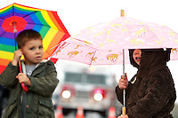 Avery Hickok, 3, takes cover from the rain as she and her brother Ethan Hickok, 4, stand outside their house Tuesday in Coeur d'Alene.
