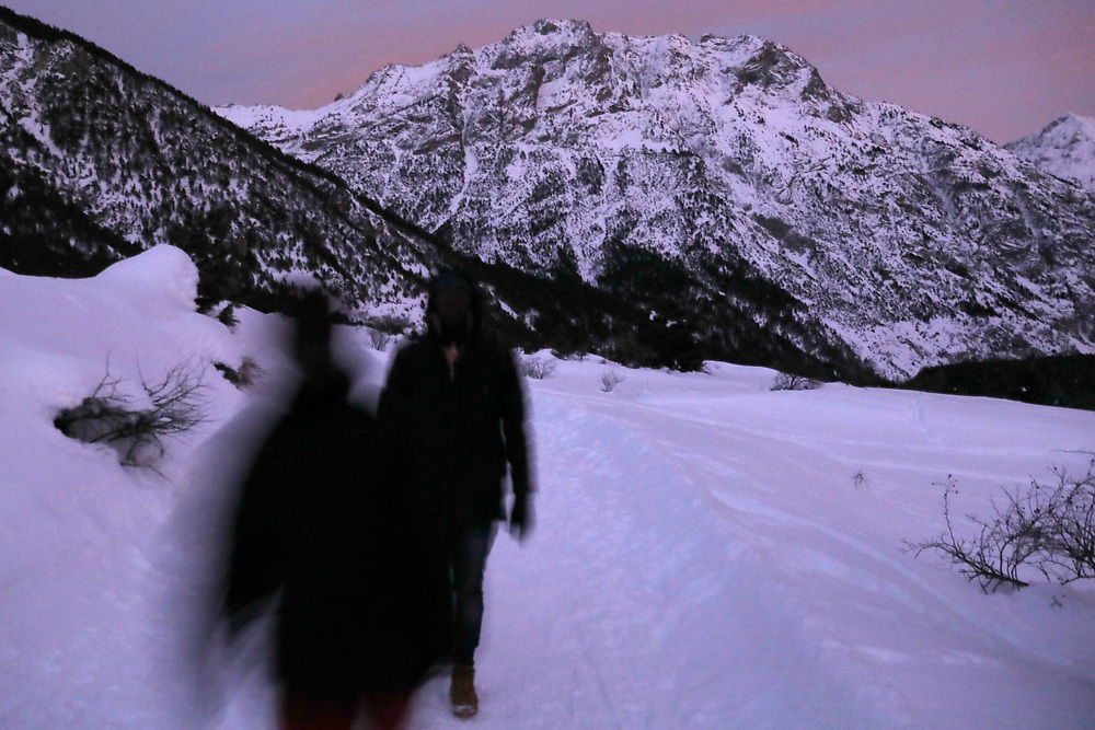 Migrants walk in snow after crossing a part of the mountain range of the Alps from Italy into France, near the town of Nevache in southeastern France.