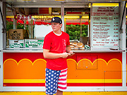 "26 JUNE 2020 - DES MOINES, IOWA: HUNTER (first name only) waits for customers at a booth selling fried potatoes and pork tenderloin sandwiches at Fair Food Friday in Des Moines. The 2020 Iowa State Fair, like many state fairs in the Midwest, has been cancelled this year because of the COVID-19 (Coronavirus) pandemic. The cancellation of the fair left many small vendors stranded with no income. Some of the fair food vendors in Iowa started ""Fair Food Fridays"" on a property a few miles south of the State Fairgrounds. People drive up and don't leave their cars while vendors bring them the usual midway fare; corndogs, fried tenderloin sandwiches, turkey legs, deep fried Oreos, lemonaide and smoothies. Fair Food Friday has been very successful. The vendors serve 450-500 people per Friday and during the lunch rush people wait in line in their cars 30 - 45 minutes to place an order.    PHOTO BY JACK KURTZ"