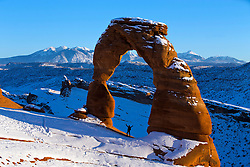 A person standing with arms up under Delicate Arch with snow in winter at sunset, Arches National Park, Utah, United States of America