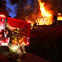 Central Firefighters pull hose from a pumper as they arrive at a fully involed home in the hills over Soquel, California on Tuesday November 4, 2008.