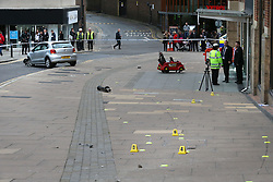 © Licensed to London News Pictures. 23/10/2015. Guilford, UK. A damaged car (top) sits in front of The Friary Centre after a number of shoppers were injured. Yellow police evidence markers line the pavement.  Photo credit: Peter Macdiarmid/LNP