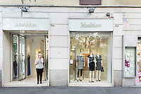 ROME, ITALY - 14 MAY 2014: Business owner Mina Giannandrea, 68, speaks on the phone at the entrance of the the Max Mara retail store she manages in Rome, Italy, on May 14th 2014. Ms. Giannandrea has owned 4 clothing store for 40 years, until last year, when she had to close two shops and fire 8 people due to high labour costs, tax hikes and big drop in domestic consumption. The shops are in two different Roman neighborhoods, and sell Max Mara garments.