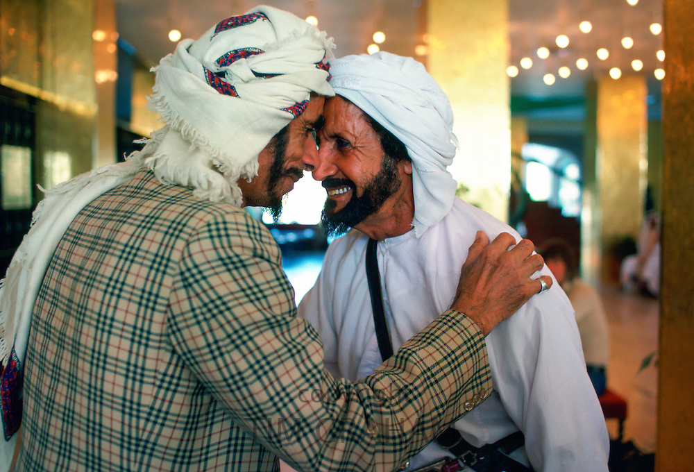 Two men wearing arab headdresses giving the traditional arab greeting in the Hilton Hotel at Al Ain, Abu Dhabi, United Arab Emirates
