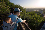 Mt. Namsan. Panoramic view over central Seoul. Mother carrying kid on her back.