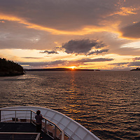 A guest watches the sunset from the bow of the National Geographic Venture in the San Juan Islands of Washington State near Jones Island Marine State Park.