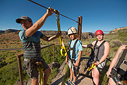 Group zip lining with the Perrine Bridge beyond in the Snake River Canyon with Zip the Snake in Twin Falls, Idaho.