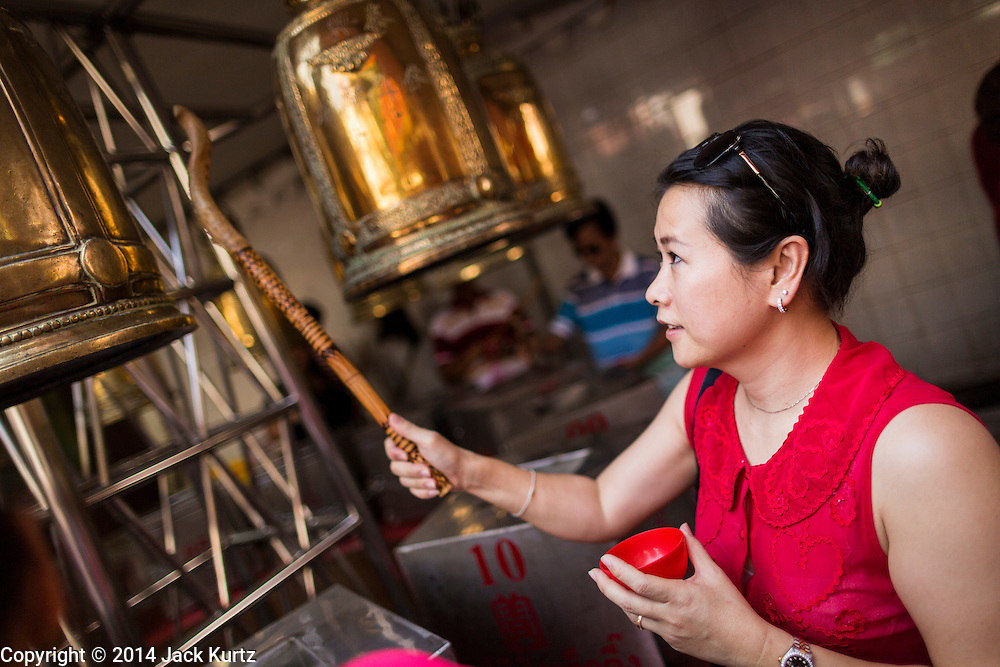 31 JANUARY 2014 - BANGKOK, THAILAND:   A woman rings prayer bells at the Poh Teck Tung Shrine during Lunar New Year festivities, also know as Tet and Chinese New Year, in Bangkok. This year is the Year of the Horse. Ethnic Chinese make up about 14% of Thailand and Chinese holidays are widely celebrated in Thailand.     PHOTO BY JACK KURTZ