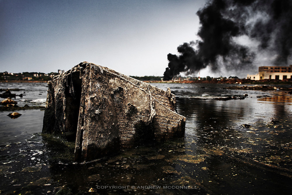 An old monitor casing lies in a polluted lagoon as smoke rises from burning e-waste, at Agbogbloshie dump, Accra, Ghana.
