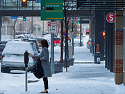 11 NOVEMBERS 2019 - DES MOINES, IOWA: A woman on a snow packed sidewalk puts money into a parking meter in downtown Des Moines Monday morning. About three inches of snow fell in the Des Moines area Sunday night into Monday morning snarling the Monday morning rush hour and delaying central Iowa schools by about two hours.       PHOTO BY JACK KURTZ