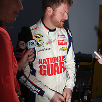 NASCAR Sprint Cup driver Dale Earnhardt Jr. (88) is interviewed in the garage area, during a NASCAR Daytona 500 practice session at Daytona International Speedway on Wednesday, February 20, 2013 in Daytona Beach, Florida.  (AP Photo/Alex Menendez)
