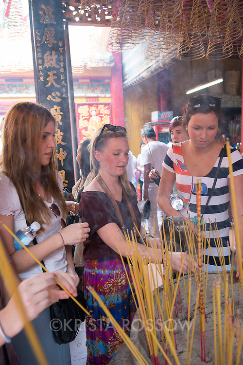 While in Vietnam, students in Professor Faye Serio's Drawing at Sea participated in a field lab in which they practiced perspective drawing while visiting multiple pagodas in Ho Chi Minh City. Jill Sabol from Florida Southern College, Michelle Anderson from Southern Methodist University, and Allegra Rumbough from Colorado College place incense in an urn at the Quan Am Pagoda in the Chinese influenced neighborhood of Cholon.
