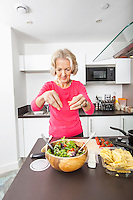 Senior woman preparing salad at kitchen counter