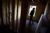 JEROME A. POLLOS/Press..Justin Miller, a building inspector with the City of Post Falls, checks the framing and insulation work on a home during an inspection Wednesday. In the wake of the nation's financial turmoil, Post Falls officials are cross training employees to help out in other areas. Miller also performs code-enforcement and business licensing duties.