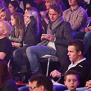 NLD/Hilversum/20110211 - 3de Liveshow SBS Sterren Dansen op het IJs 2011, John Ewbank met dochter Day op schoot checked zijn telefoon
