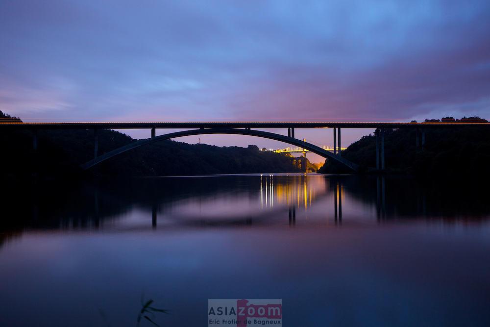 Le pont du Morbihan qui enjambe la Vilaine a la Roche brenard au petit matin. <br /> Le pont fut construit entre 1993 et 1995 dans le cadre de la d&eacute;viation de la RN165 (Nantes - Brest). Cette d&eacute;viation permet de d&eacute;sengorger La Roche-Bernard devenue c&eacute;l&egrave;bre pour ses embouteillages estivaux pouvant atteindre 20 km. L'ancien pont de La Roche-Bernard de type suspendu inaugur&eacute; en 1960 n'avait en effet que 2 voies de circulation, il &eacute;tait devenu urgent de le remplacer devant la croissance du trafic automobile (env. 40,000 v&eacute;hicules/jour en &eacute;t&eacute; &agrave; l'&eacute;poque). L'arc est constitu&eacute; de 55 voussoirs : 2 fois 27 &eacute;l&eacute;ments de 3.90 m, chacun d'environ 100 tonnes, et une cl&eacute; de vo&ucirc;te de 80 cm. Chaque voussoir fait 8.25 m de large, leur hauteur variant entre 3.50 m au pied &agrave; 2.90 m &agrave; la cl&eacute;. L'arc comporte 2 escaliers pour permettre aux pi&eacute;tons de franchir la Vilaine sous le tablier qui est r&eacute;serv&eacute; exclusivement &agrave; la circulation de v&eacute;hicules. Le sommet de l'arc est &agrave; un peu plus de 27 m au-dessus de la Vilaine. Le tablier d'une largeur de 20,30 m et &agrave; ossature mixte (b&eacute;ton, acier) accueille quatre voies r&eacute;serv&eacute;es aux v&eacute;hicules, 2 voies dans chaque sens s&eacute;par&eacute;es par un muret en b&eacute;ton. Le tablier repose sur des pilettes espac&eacute;es de 32 &agrave; 36 m. (source Wikipedia)