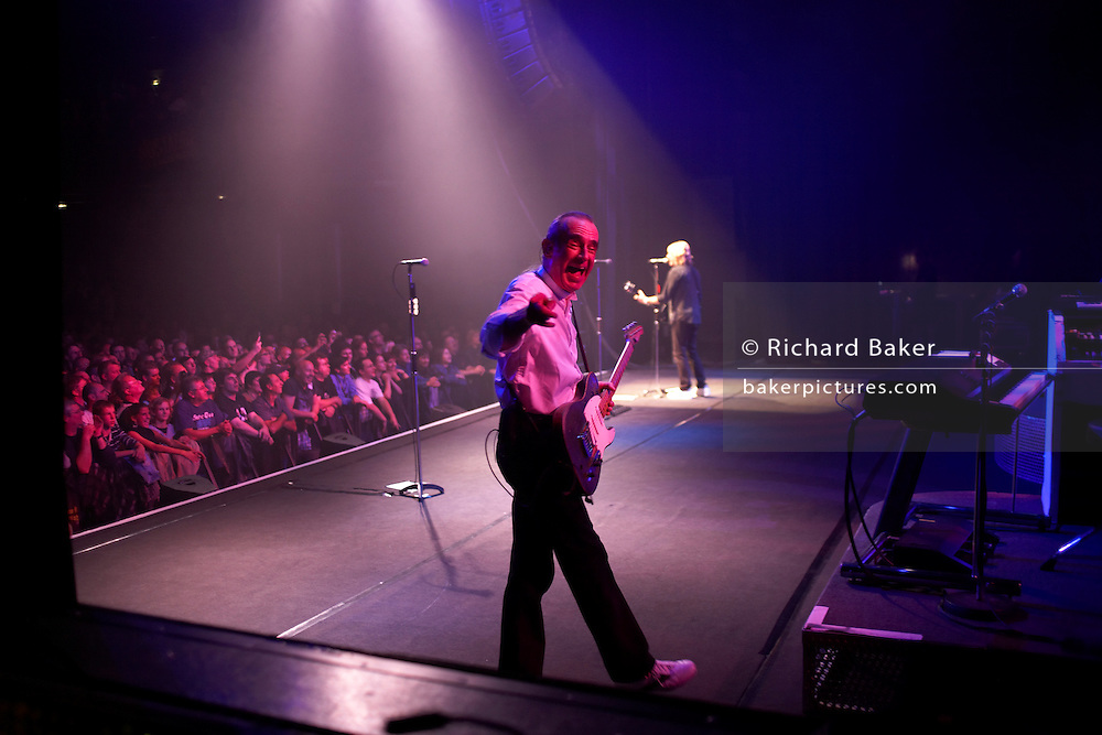 On stage during their show, Francis Rossi (foreground) and Rick Parfitt of the band Status Quo play from their 90-minute repertoire of classic rock and roll songs. We see Rossi pausing to point to the photographer as Parfitt plays facing the audience whose front row members are jumping up and down in time with the beat, in l'Aeronef in Lille, France during their 2007 European Tour. Parfitt and Rossi are the two original members of the band, having met as school boys in the early 60s. Their distinctive three-chord guitar riff has made them a household name with hits like: Rockin' All Over the World and Sweet Caroline; selling 118 million albums. Over their 40 years of performing, QUO have played over 6000 live shows to an audience of 25 million people and travelling four million miles and spent 23 years away from home.