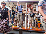 15 OCTOBER 2014 - BANGKOK, THAILAND:  Tourists disembark from a Chao Phraya Express Boat on the Chao Phraya River in Bangkok. The number of tourists arriving in Thailand in July fell 10.9 per cent from a year earlier, according to data from the Department of Tourism. The drop in arrivals is being blamed on continued uncertainty about Thailand's political situation. The tourist sector accounts for about 10 per cent of the Thai economy and suffered its biggest drop in visitors in June - the first full month after the army took power on May 22. Arrivals for the year to date are down 10.7% over the same period last year.   PHOTO BY JACK KURTZ