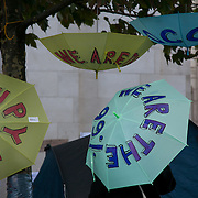 Umbrellas hanging of a tree. Day three of the occupation - and the first Monday.  The Occupy London Stock Exchange movement was formed in London in solidarity with the US based Occupy Wall Street. The movements are a respons and in anger to what is seen by many as corporate greed and a failed banking system being bailed out by the public, - which in return are suffering austerity measures to make up for the billions of lost money. The movement occupied the St Paul's Square in the City of London Sat Oct 15 after it failed to secure and occupy Pator Noster Square and the Stock Exchnage itself.