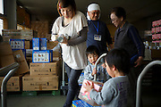 A pregnant mother of two twin boys are recieving survival kits at the NPO Bridge For Fukushima at a warehouse that doubles up as an indoor playground for children and a food distribution centre for residents who fear eating the local produce and drinking the tap water. Minamisoma, Fuksushima Prefecture.