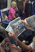 London commuters read the Evening Standard newspaper on the tube