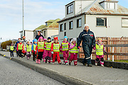 A class of school children wearing  florescent vests and snow suits walk with teachers in a small fishing village in Iceland.