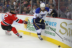Feb 9; Newark, NJ, USA; St. Louis Blues defenseman Kris Russell (4) skates with the puck while being defended by New Jersey Devils left wing Alexei Ponikarovsky (12) during the second period at the Prudential Center.